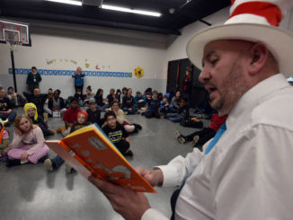 Students at New Story School in Wyoming listen intently as Swoyersville mayor reads