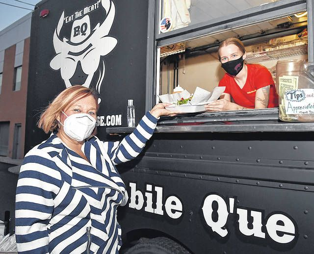 <p>Mary Butera, left, grabs a meal from participating food vendor Alissa Dorsey of B3Q Smokehouse.</p>                                  <p>Tony Callaio | For Sunday Dispatch</p>