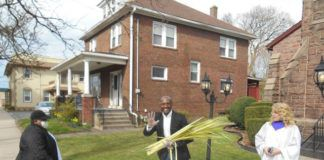 Pastor Adam McGahee, center, and his wife, Lisa, were giving out palm branches outdoors in front of Moving River Ministries, 439 S. Main St., Wilkes-Barre last year. The church's Praise Team will be handing them out again this year, from 10 a.m. to noon on March 28.                                  Mary Therese Biebel   Times Leader file photo